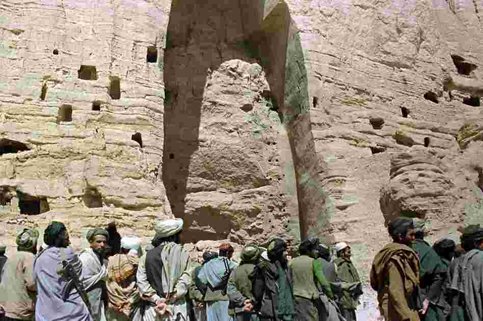 Taliban soldiers stand at the base of a mountain alcove under one of the destroyed Buddha statues in March 2001.