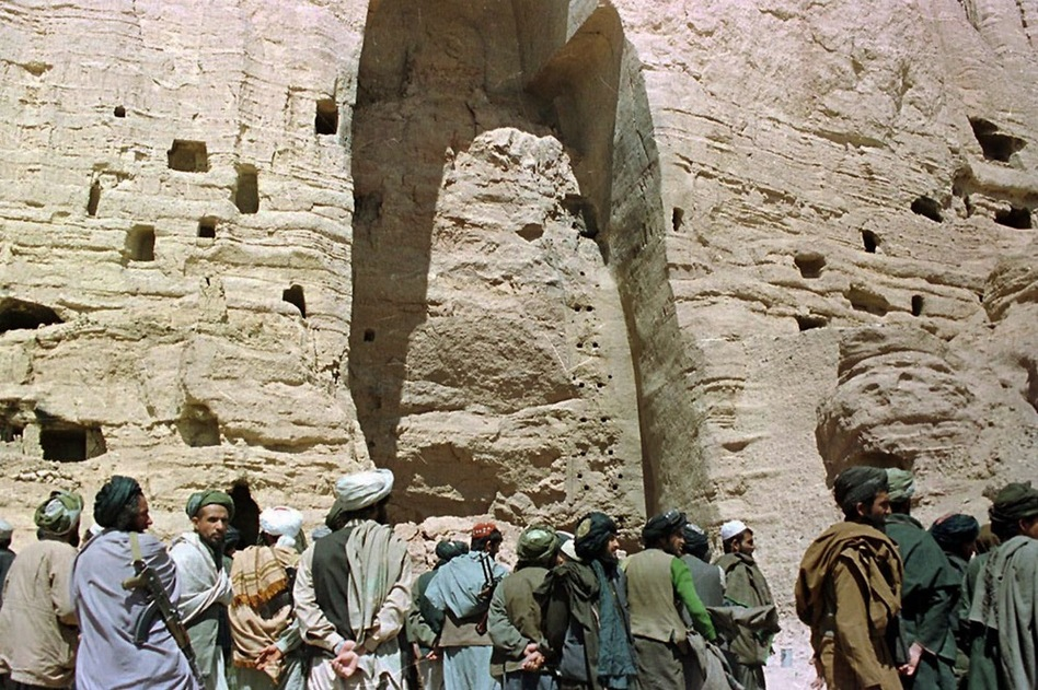 Taliban soldiers stand at the base of a mountain alcove under one of the destroyed Buddha statues in March 2001.  (AP)