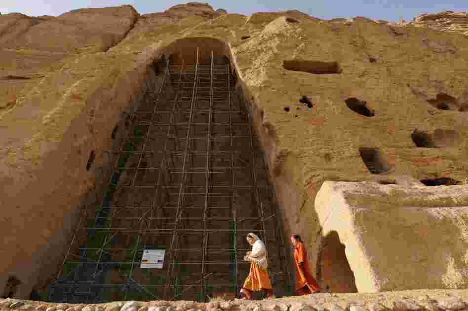 Afghan girls walk past scaffolding at the site of one of the destroyed Buddha statues in this 2008 photo. Some Bamiyan residents support the restoration project. Others say the statues should not be rebuilt, to remind people of the Taliban's fanaticism.