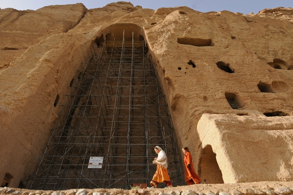 Afghan girls walk past scaffolding at the site of one of the destroyed Buddha statues in this 2008 photo. Some Bamiyan residents support the restoration project. Others say the statues should not be rebuilt, to remind people of the Taliban's fanaticism.  (AFP/Getty Images)