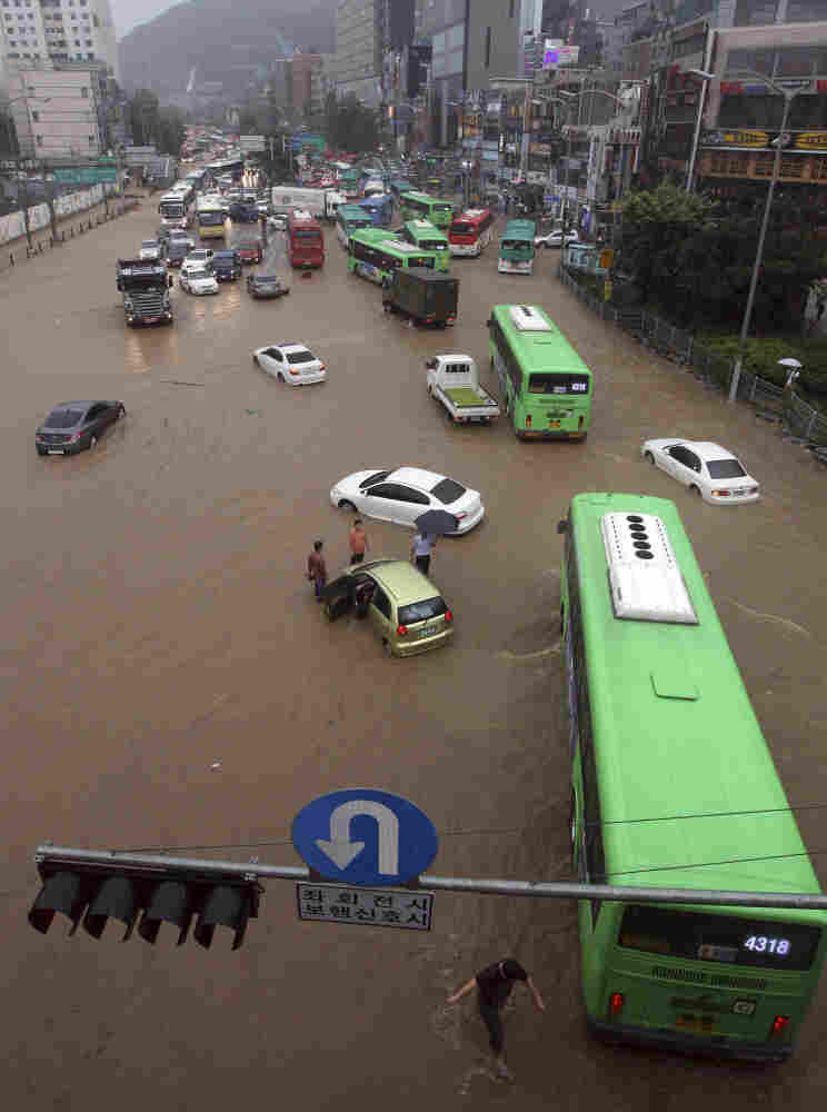 Vehicles dotted a flooded road in Seoul on Wednesday. Officials said heavy rains and landslides have left about 620 people homeless.