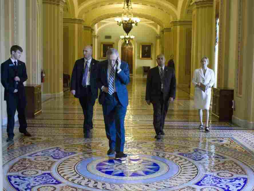 Senate Majority Leader Harry Reid on his cellphone as he walks to his office, July 27, 2011.
