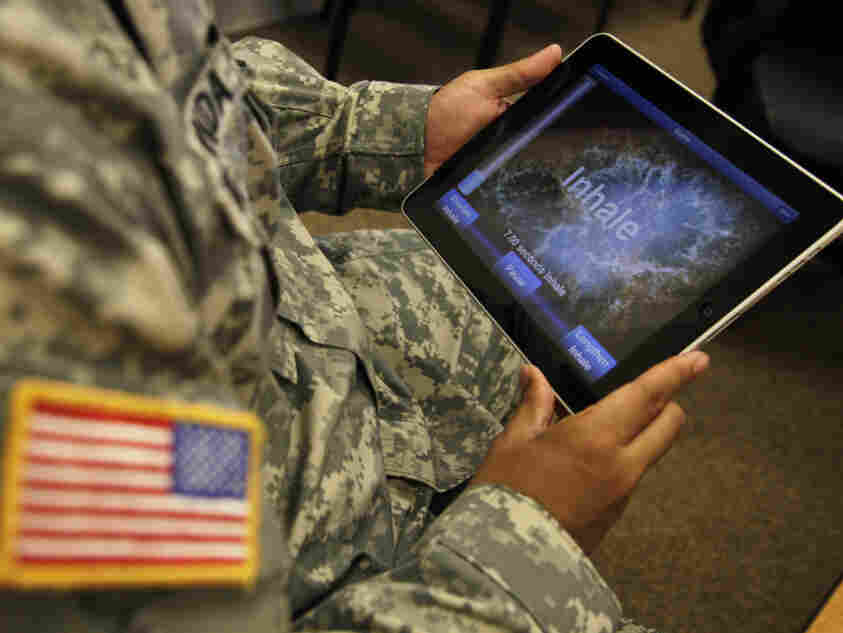 A serviceman, holds an iPad equipped with an app for to help soldiers suffering from PTSD.