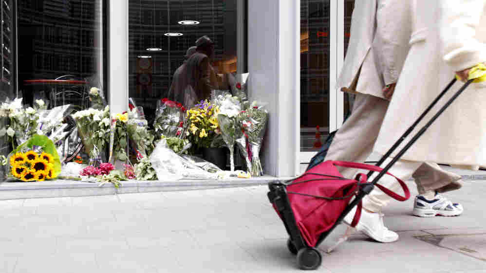 Two people walk by a flower memorial in front of the Norway House in Brussels on Thursday, July 28, 2011. The EU convened a special meeting on counterterrorism in Brussels on Thursday, following the Norway massacre, in which at least 76 people were killed.