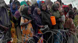 Internally displaced Somalis wait for food at a distribution point at the government-run Badbaado refugee camp in a suburb of the capital Mogadishu on Tuesday. The U.N.'s World Food Programme said its airlift to Mogadishu for drought victims was delayed Tuesday because of last-minute bureaucratic hurdles in Kenya.