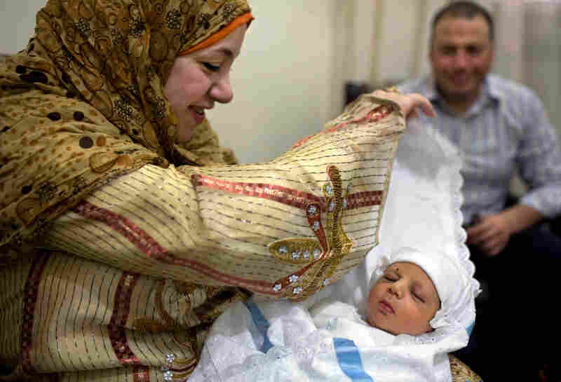Israa Saad Diab lifts the cover from her son Hamza's face, while her husband, Ibrahim Muhammad, watches, after the traditional Sebou ceremony in Mansoura, Egypt, on May 27.