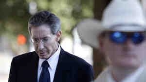 A law enforcement official stands by as Polygamist sect leader Warren Jeffs, left, arrives at