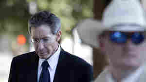"A law enforcement official stands by as Polygamist sect leader Warren Jeffs, left, arrives at the Tom Green County Courthouse on Thursday in San Angelo, Texas. Jeffs' much-anticipated Texas trial began on Thursday, with prosecutors claiming he sexually assaulted girls he manipulated into ""spiritual marriage,"" and defense attorneys countering that their client's religious freedoms were trampled."