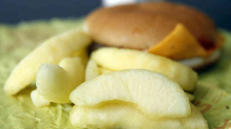 A McDonald's Cheeseburger Happy Meal with apple slices, which are becoming standard fare.