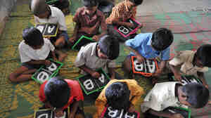 Indian schoolchildren write English alphabets on slates at a primary school outside Hyderabad in June. India is on track to
