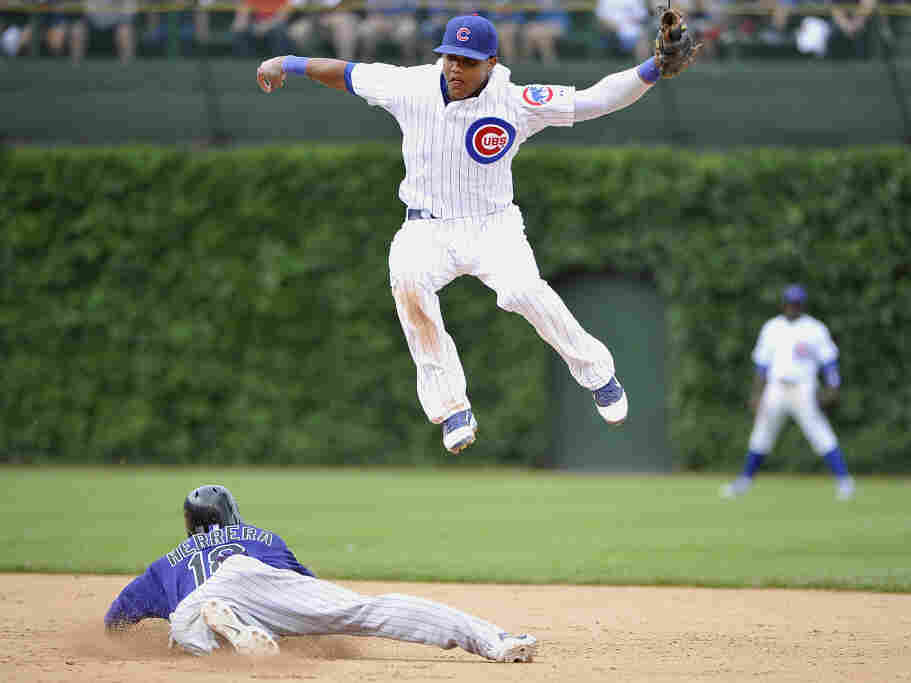 Jonathan Herrera of the Colorado Rockies slides into second as shortstop Starlin Castro of the Chicago Cubs leaps for a wild throw from catcher Geovany Soto at Wrigley Field on June 27.