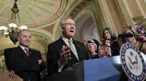Senate Majority Leader Harry Reid of Nevada (center), accompanied by Sen. Charles Schumer, D-N.Y. (left), tells reporters that he is moving ahead with a Democratic plan