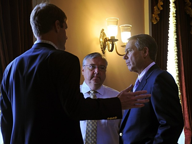 House Speaker John Boehner (right) consults with staff members before entering the House chamber on Saturday. (AFP/Getty Images)