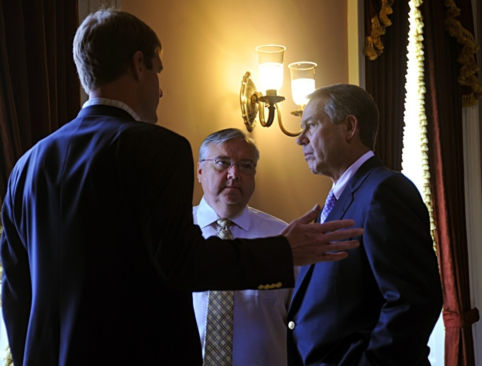 House Speaker John Boehner (right) consults with staff members before entering the House chamber on Saturday.