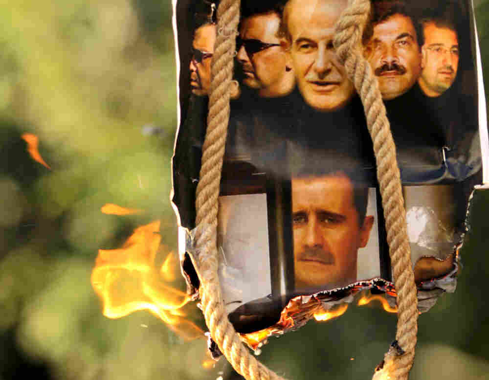 A makeshift gallows with a poster shows the pictures of former Syrian president Hafez Assad, and his sons, including current President Bashar Assad.
