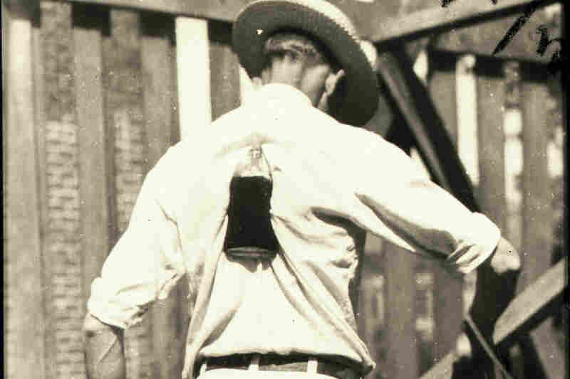 Henry Gibbs of Old Fort, N.C., lifts a whiskey bottle with his shoulder blades, 1931.
