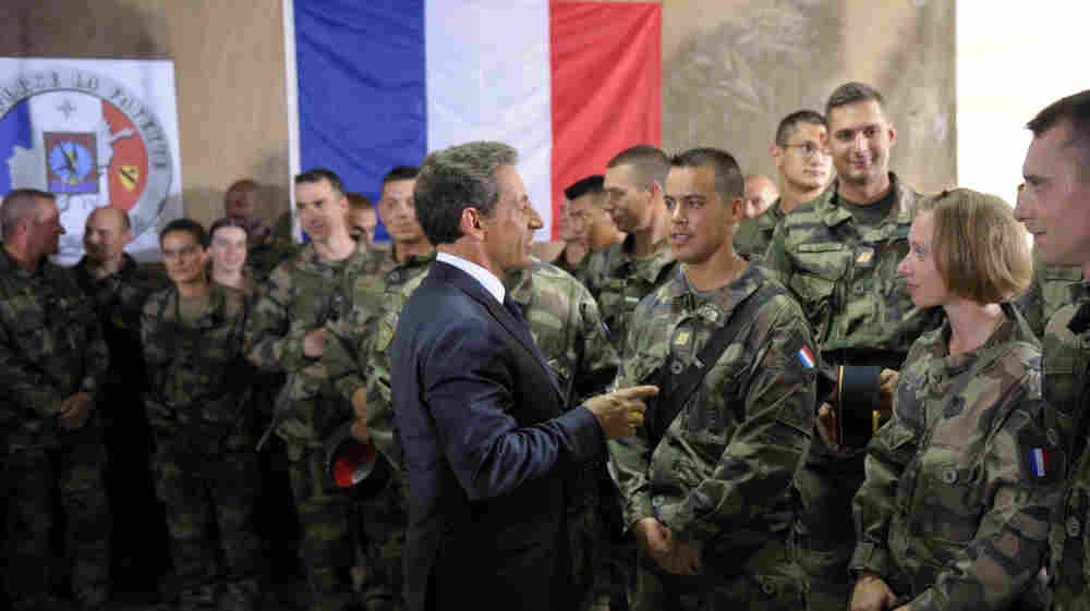 French President Nicolas Sarkozy speaks with French troops at the 152nd Infantry Regiment military base in the region of Surobi, Afghanistan, in July. Analysts say the French military has been strained by restructuring, budget cuts and simultaneous conflicts abroad.