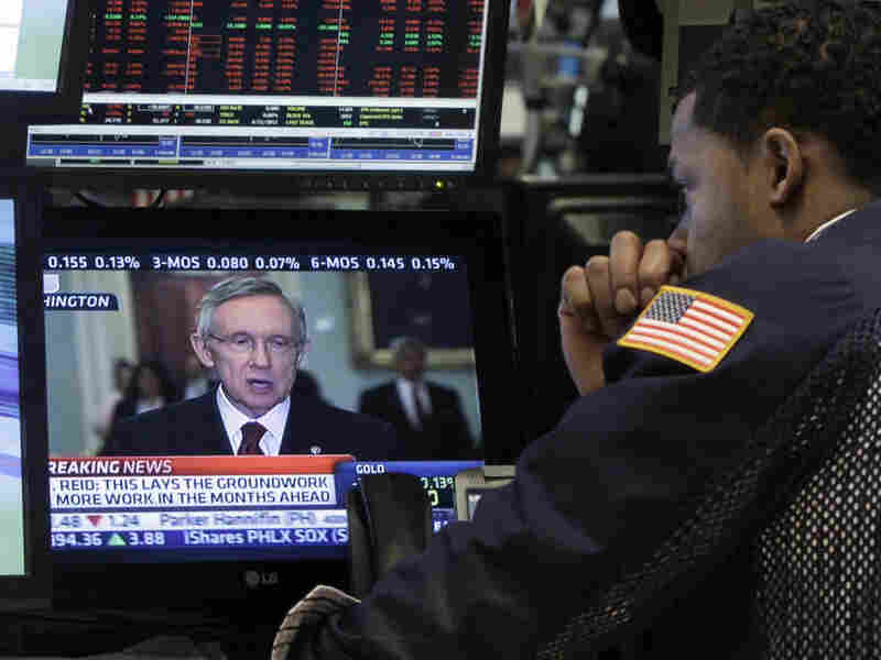 A specialist on the floor of the New York Stock Exchange watches Sen. Harry Reid talk on television Monday.