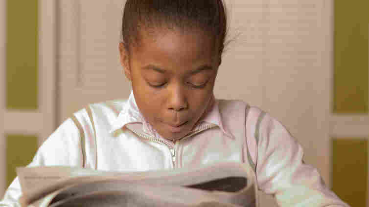 Young girl reading the newspaper.