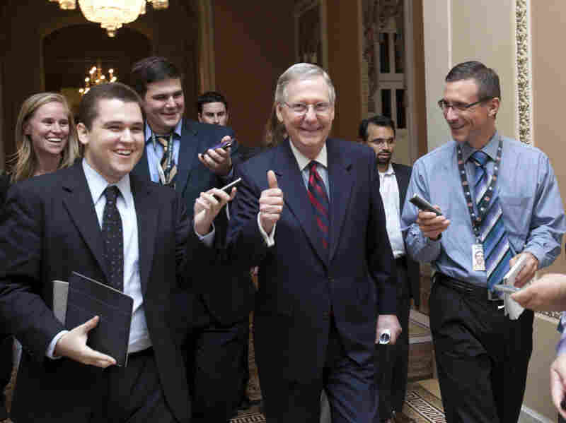 Senate Republican Leader Mitch McConnell of Kentucky (center) walks to the Senate floor to announce that a deal has been reached on the debt ceiling on Capitol Hill on Sunday.