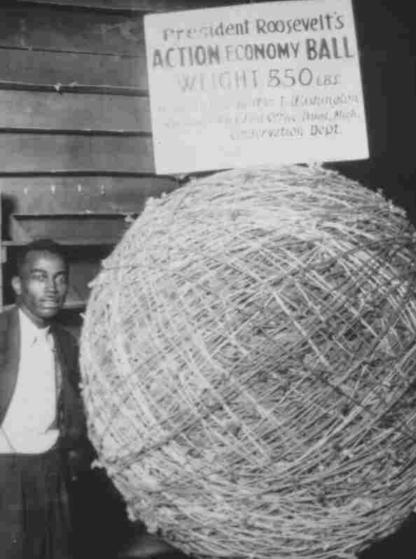 "William T. Washington poses with a ""hand tailored,"" 850-pound ball of string, 1933. The ball was six feet in diameter."