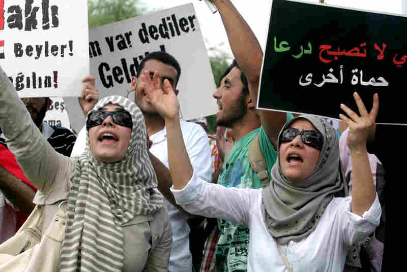 """Members of a pro-Islamic human rights group hold up a sign that reads """"We remember Hama"""" during a protest against the Syrian regime Monday in Ankara, Turkey."""