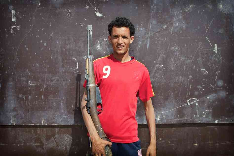 A Libyan rebel poses with his antique bolt-action rifle. He said that it was an American-made 1911; it is actually an Italian-made Carcano.