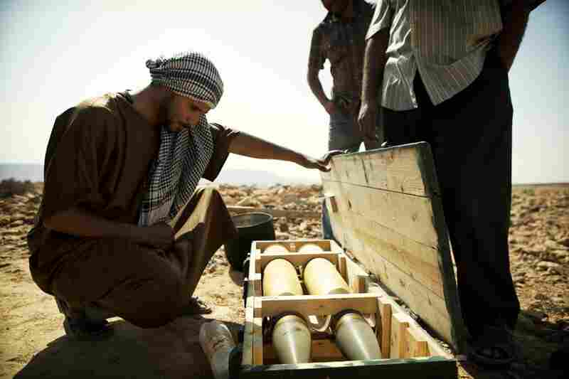 A rebel looks at a crate containing two 100mm rounds for the main gun of a T-55 battle tank that had previously belonged to Moammar Gadhafi's forces.
