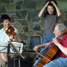 Violinist Soovin Kim, pianist Mitsuko Uchida and cellist David Soyer caught in a light moment at the Marlboro Music Festival