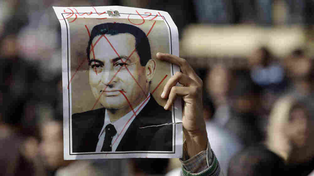 """A protester holds a defaced poster of Egypt's then-President Hosni Mubarak, with the words """"Mubarak, get out,"""" during an anti-government demonstration in Cairo in January. Mubarak now faces trial on charges of  corruption and ordering the killing of protesters  during the uprising earlier this year that led to the end of his 30-year rule."""