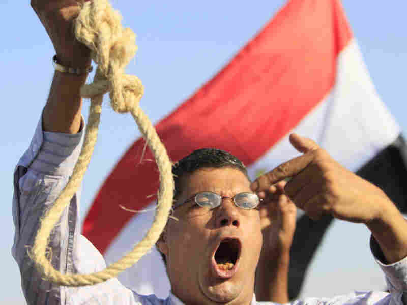 An anti-Mubarak protester flashes a noose during a protest outside the police academy in Cairo on Wednesday.