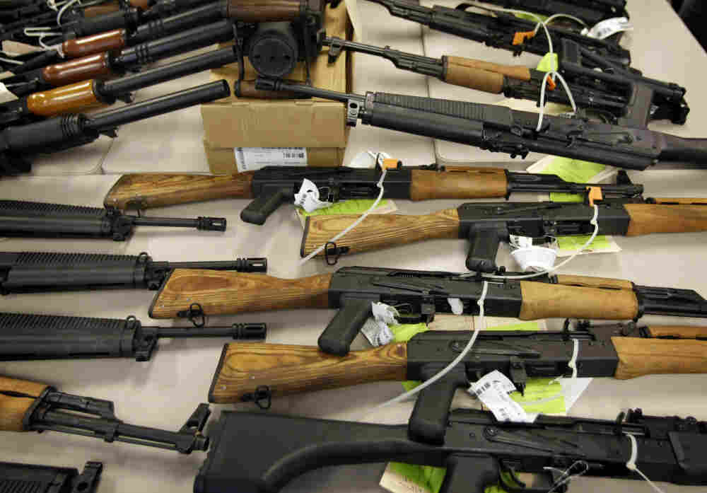 A photo taken in January shows part of a cache of seized weapons displayed at a news conference in Phoenix. In July, the Justice Department announced new rules requiring gun dealers to report multiple sales of semi-automatic rifles.