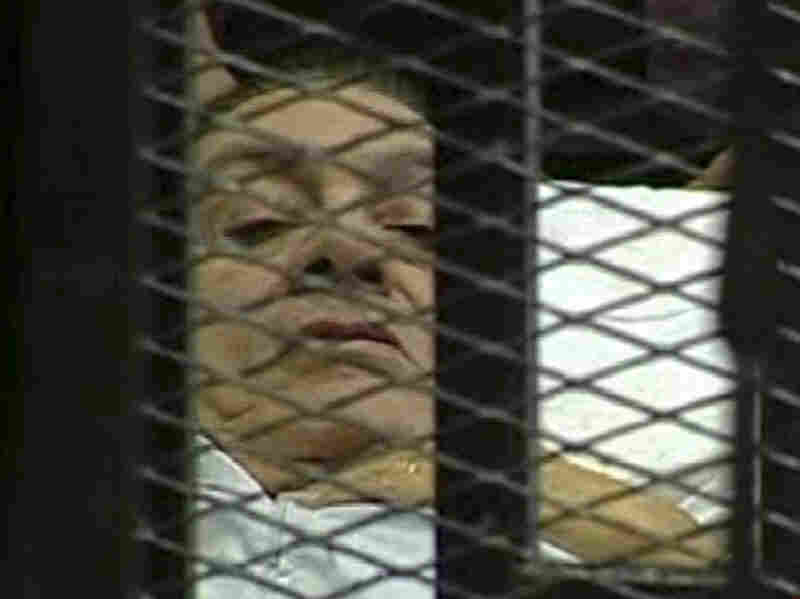 This video image taken from Egyptian state television shows former President Hosni Mubarak laying on a hospital bed inside a cage of mesh and iron bars in a Cairo courtroom as his trial began Wednesday.