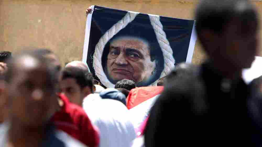 Egyptians walk past a poster of Egypt's ousted president Hosni Mubarak shown  behind a noose outside the court set up in the Cairo Police Academy, on August 3.
