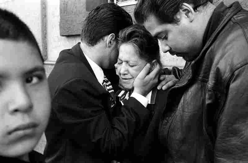 Chi Chi's mother and brothers cry at his funeral. Chi Chi, an innocent bystander, was murdered during a hit on a drug dealer,  1990s.