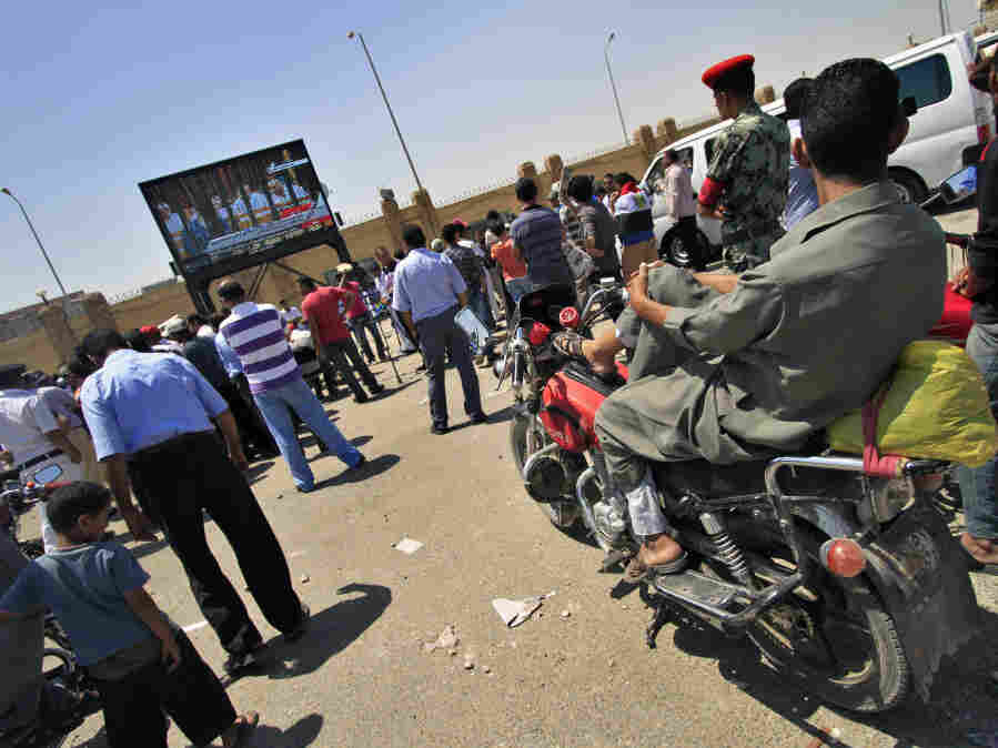 People watch the trial of former Egyptian Interior Minister Habib el-Adly and six top police officials live on a TV screen outside the Police Academy complex in Cairo, Egypt Thursday, Aug. 4, 2011. A day after the start of Hosni Mubarak's trial, seven of his co-defendants are back in the courtroom on charges of ordering the killing of protesters during uprising that toppled Egypt's president.