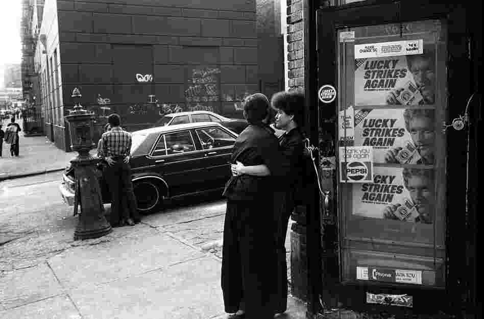 Teenage couples kiss on the street corner, 1980s