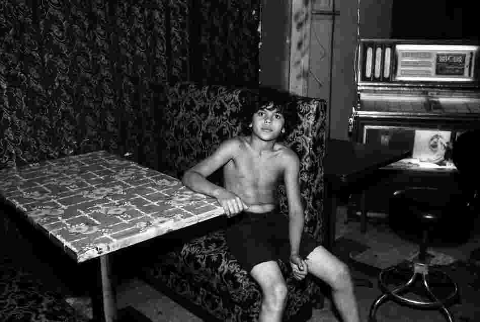 Boy sits at table in adult social club, 1980s