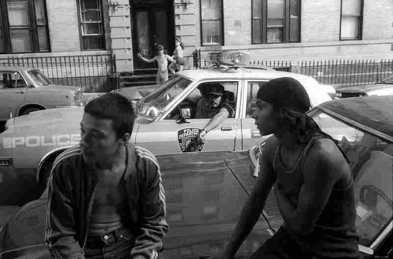 New York City police stop their car to check out two youths, who are not selling drugs, but who are hanging out on a known drug corner,  1980s.