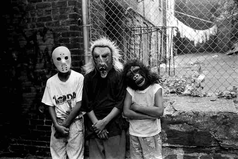 Three teenage boys wear Holloween masks, 1990s