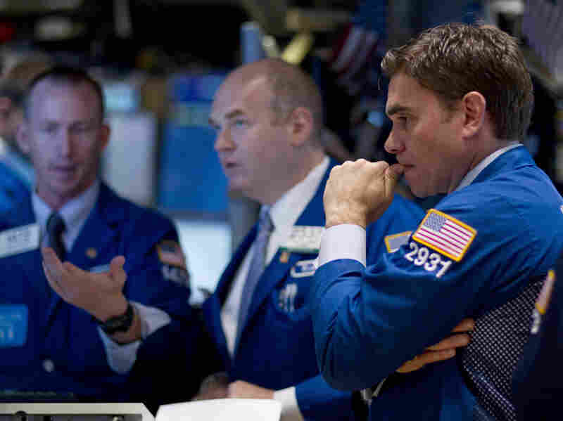 Traders work on the floor of the New York Stock Exchange on Thursday. Stocks sank again as investors continued to fret about the struggling economies in Europe and slow growth in the U.S.
