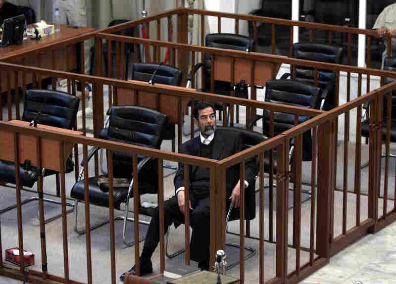 Former Iraqi President Saddam Hussein sits alone in the defendant's cage during cross-examination at his 2006 trial in Baghdad. Saddam and seven co-defendants were charged with massacring 148 villagers from the town of Dujail. Saddam was sentenced to death and executed later that year.