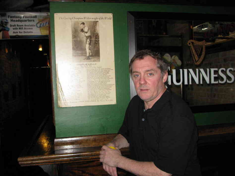 Michael Harvey stands next to a poster of his great-great-uncle Charlie Kelly at his Lincoln Park bar. Harvey's main character, Michael Kelly, was named after Charlie's father.