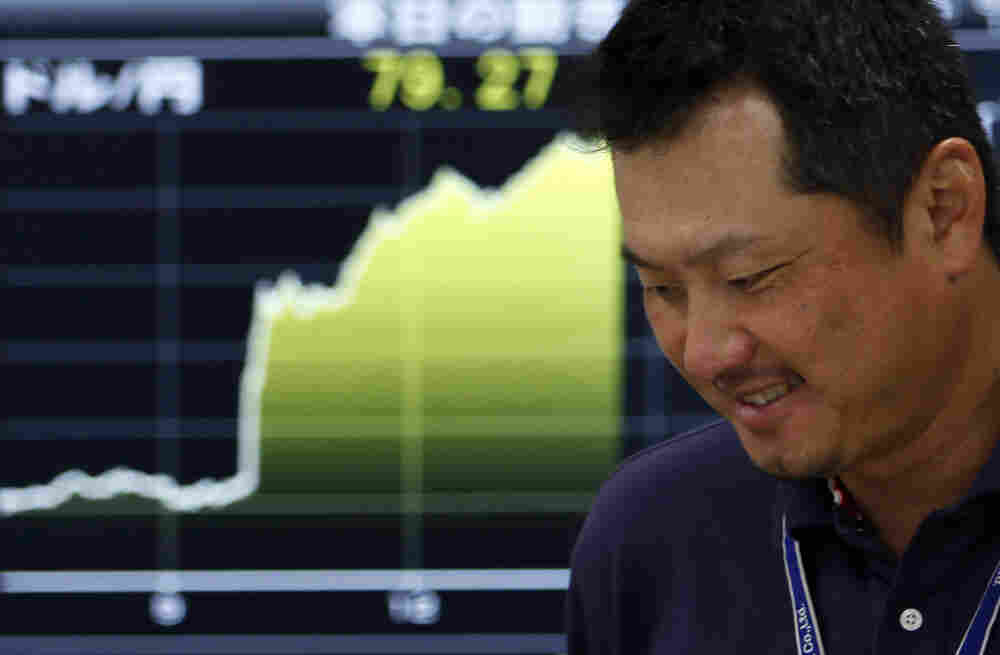A money trader reacts in front of the  yen-dollar exchange rate at  a money market brokerage firm in Tokyo.