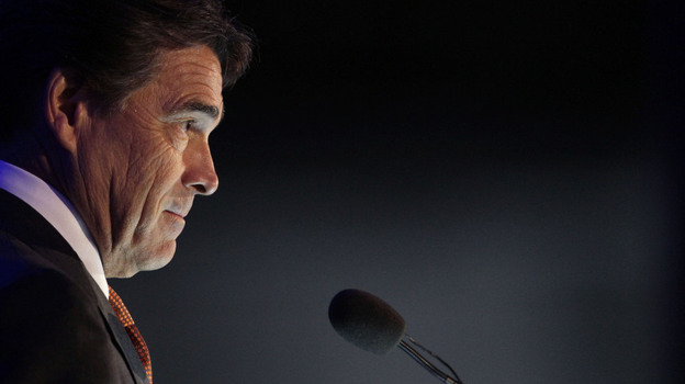 """Texas Gov. Rick Perry looks on during a speech at a Boy Scout ceremony in June aboard the USS Midway in San Diego. At that dinner, he said the federal government is rudderless. Now, he's calling for a """"day of prayer and fasting on behalf of our nation."""" (AP)"""