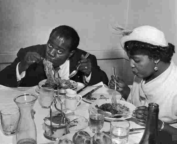Louis Armstrong tucks into a plate of spaghetti in Rome with his wife Lucille in 1949.