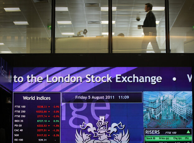 A worker walks past screens showing stock market price falling at The London Stock Exchange on August 5.