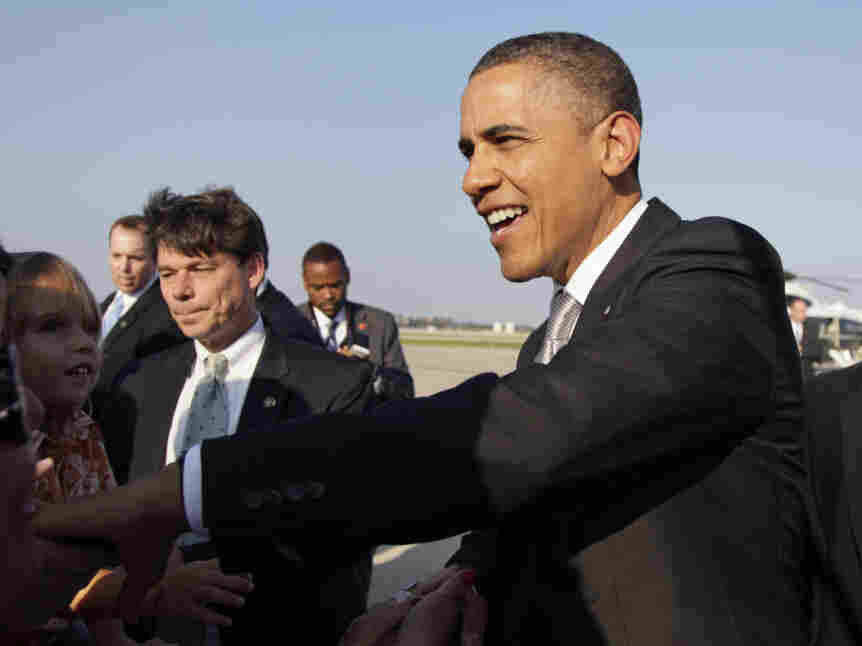 President Barack Obama greets people waiting  for him on the tarmac as he arrives on Air Force One at O'Hare International Airport, Wednesday, Aug. 3, 2011, in Chicago.