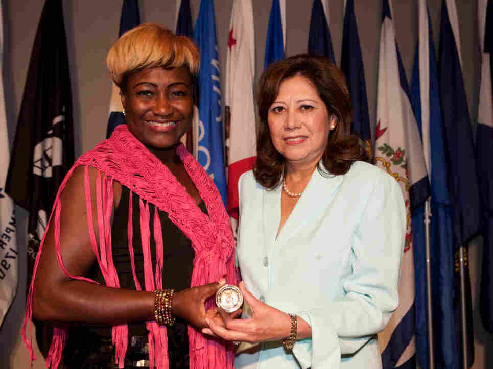 """Lisa Bolling accepts the """"Challenge Coin"""" from Secretary of Labor Hilda L. Solis at Arlington National Cemetery's Women in Military Service for America Memorial on July 20. The secretary shared Bolling's story of being a homeless female veteran at the launch of a new trauma guide for women."""