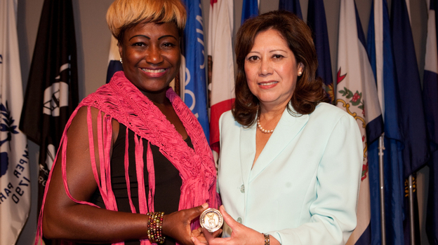 "Lisa Bolling accepts the ""Challenge Coin"" from Secretary of Labor Hilda L. Solis at Arlington National Cemetery's Women in Military Service for America Memorial on July 20. The secretary shared Bolling's story of being a homeless female veteran at the launch of a new trauma guide for women. (Courtesy Of The Department Of Labor)"